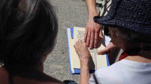 visite tactile au jardin botanique, 2 mains au contact d'un document